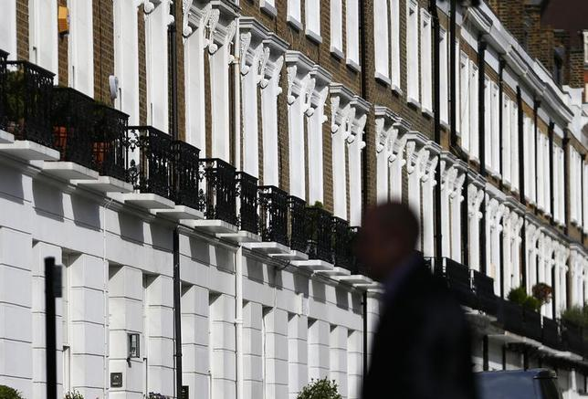 A man walks past a row of houses in Chelsea in London August 13, 2013. REUTERS/Andrew Winning