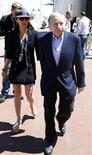 Former Ferrari team manager and FIA President Jean Todt and his girlfriend Michelle Yeoh walk in the paddock area before the Monaco F1 Grand Prix May 26, 2013. REUTERS/Stefano Rellandini