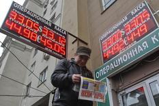 Мужчина с газетой проходит под вывеской пункта обмена валют в Москве 28 ноября 2013 года. Рубль подорожал на пятничной сессии за счет сокращения длинных валютных позиций, преобладавших на рынке, перед трудовой статистикой США, которая может повлечь за собой резкий рост волатильности в конце дня. REUTERS/Maxim Shemetov