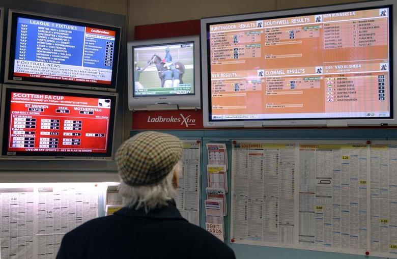 A man watches television screens in a Ladbrokes bookmaker in London February 19, 2009. REUTERS/Luke MacGregor