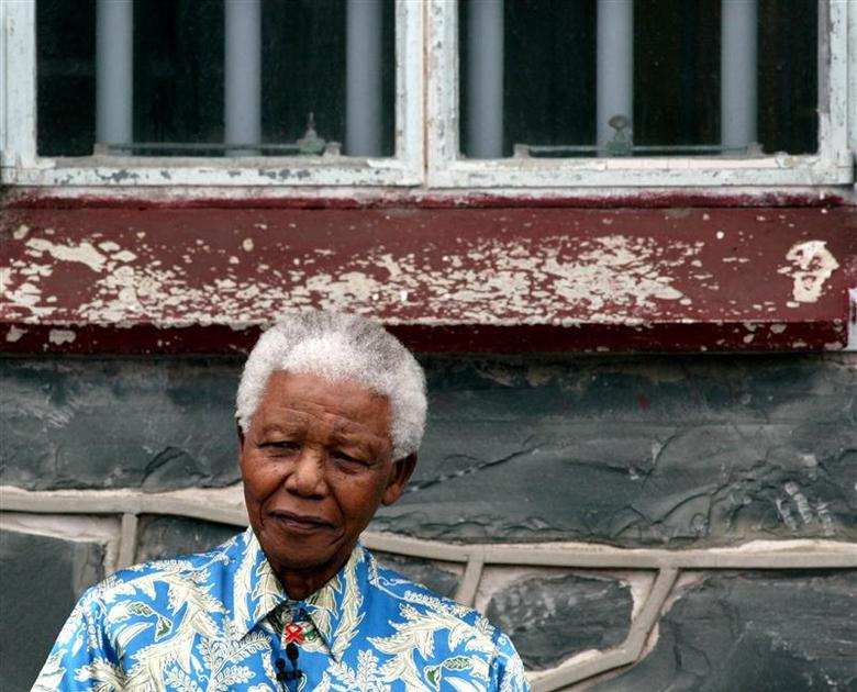 Nelson Mandela sits beneath the window of his prison cell on Robben Island near Cape Town, November 28, 2003. REUTERS/Mike Hutchings
