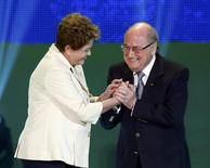 Brazilian President Dilma Rousseff (L) and FIFA President Sepp Blatter react on stage during the draw for the 2014 World Cup at the Costa do Sauipe resort in Sao Joao da Mata, Bahia state, December 6, 2013. REUTERS/Sergio Moraes