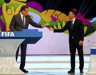 Former Italy soccer player Fabio Cannavaro (R) hands a ball that he had drawn from a pot to FIFA Secretary General Jerome Valcke during the draw for the 2014 World Cup at the Costa do Sauipe resort in Sao Joao da Mata, Bahia state, December 6, 2013. REUTERS/Sergio Moraes