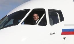 Премьер-министр России Дмитрий Медвеедв выглядывает из окна кабины лайнера Sukhoi Superjet 100 на авиасалоне в Жуковском 27 августа 2013 года. Столкнувшаяся с дефицитом пилотов Россия готовится разрешить авиакомпаниям нанимать иностранцев. REUTERS/Ekaterina Shtukina/RIA Novosti/Pool