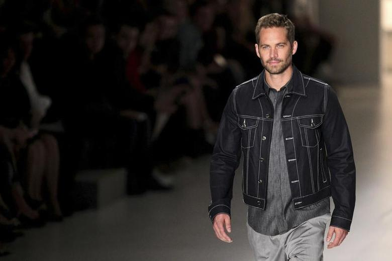 U.S. actor Paul Walker presents a creation from Colcci's 2013/2014 summer collection during Sao Paulo Fashion Week March 21, 2013. REUTERS/Filipe Carvalho