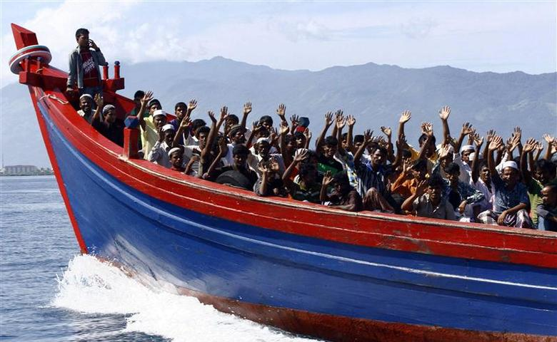 Ethnic Rohingya refugees from Myanmar wave as they are transported by a wooden boat to a temporary shelter in Krueng Raya in Aceh Besar, in this file picture taken April 8, 2013. REUTERS/Junaidi Hanafiah/Files