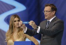 El secretario general de la FIFA, Jerome Valcke, sostiene el papel que muestra el nombre de Holanda junto a la presentadora Fernanda Lima durante el sorteo de la Copa del Mundo 2014 en Costa do Sauípe, en Sao Joao da Mata, estado de Bahía. 6 de diciembre, 2013. REUTERS/Ricardo Moraes (BRASIL - DEPORTES FUTBOL MUNDIAL)