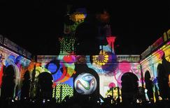 "People take pictures of the official match ball for the 2014 World Cup named ""brazuca"" which is projected on a building at Lage Park during a presentation ceremony in Rio de Janeiro in this December 3, 2013 file photo. REUTERS/Stringer/Files"