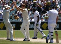 England's Michael Carberry (2nd R) walks off the field after his dismissal, as Australia's Shane Watson (2nd L) and Ryan Harris (L) celebrate, during the third day of the second Ashes test cricket match at the Adelaide Oval December 7, 2013. REUTERS/David Gray