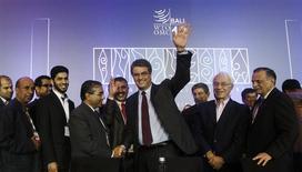L'Organisation mondiale du Commerce (OMC), dirigée depuis septembre par le Brésilien Roberto Azevedo (au centre), a scellé samedi un accord qualifié d'historique sur le commerce mondial, le premier depuis sa création il y a près de 19 ans, en janvier 1995. Réunis à Bali depuis mardi, les ministres des 159 Etats membres de l'organisation ont adopté à l'unanimité un ensemble de réformes sur la facilitation des échanges, l'agriculture et le développement. /Photo prise le 7 décembre 2013/REUTERS/Edgar Su
