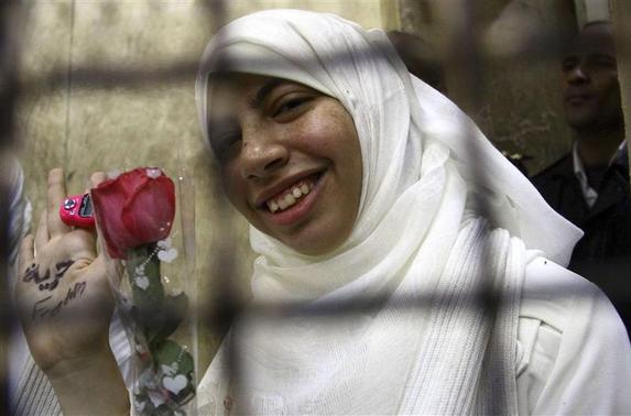 Alaa Osama al-Araky, 22, who was found guilty along with other women and girls of obstructing traffic during a pro-Islamist protest in October, smiles during an appeal hearing at a court in the Mediterranean city of Alexandria, 230 km (143 miles) north of Cairo December 7, 2013. REUTERS-Stringer