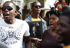 People dance during a gathering of mourners on Vilakazi Street in Soweto, where the former South African President Nelson Mandela resided when he lived in the township, December 7, 2013. REUTERS/Yves Herman