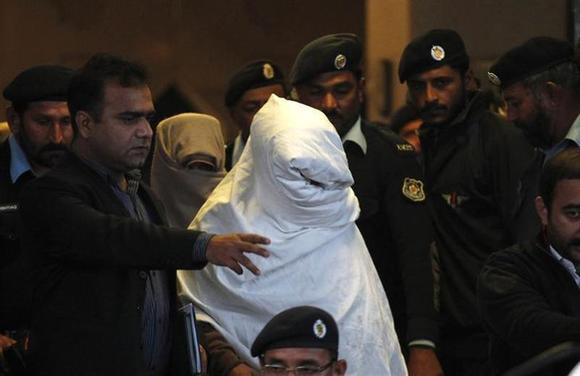 Security officials and police officers escort men, who cover themselves with cloth, as they leave after appearing before the Supreme Court in Islamabad December 7, 2013. REUTERS/Mian Khursheed