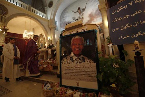 A poster depicting former South African President Nelson Mandela is displayed during a special service in his honour at the Holy Family Church in the West Bank city of Ramallah December 8, 2013. REUTERS/Mohamad Torokman