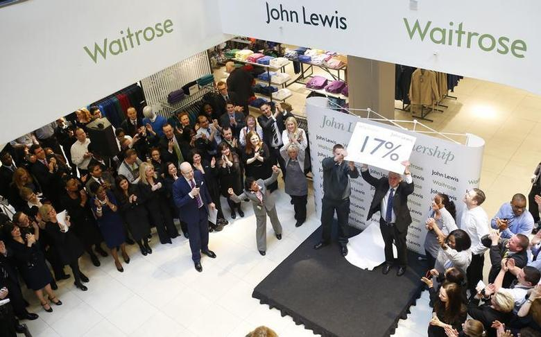 Workers, known as partners at the John Lewis Partnership, celebrate as their annual profit related bonus is announced by the manager, at their flagship Oxford Street store in central London March 7, 2013. REUTERS/Andrew Winning