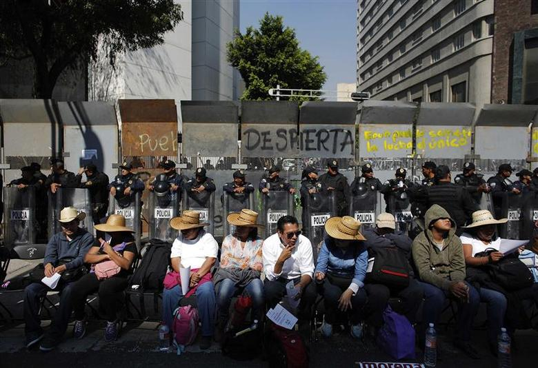 Demonstrators sit in front of riot policemen during a protest against the energy reform bill outside the Senate building in Mexico City December 6, 2013. REUTERS/Tomas Bravo