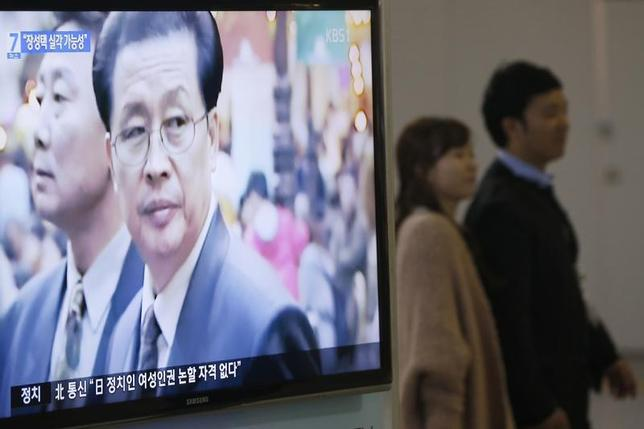 A couple walks past a television showing a report on Jang Song Thaek, North Korean leaders' uncle, at a railway station in Seoul December 3, 2013. REUTERS/Kim Hong-Ji