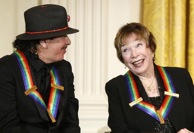 Carlos Santana (L) and fellow 2013 Kennedy Center Honors recipient Shirley MacLaine react to remarks by U.S. President Barack Obama (not pictured) during a reception at the White House in Washington December 8, 2013. REUTERS/Jonathan Ernst