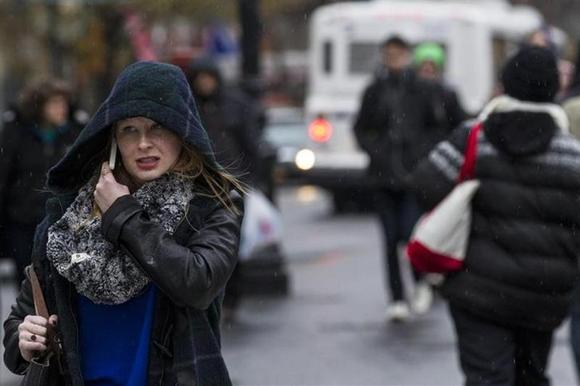 A woman talks on her mobile phone as the rain begins to fall in New York November 26, 2013. REUTERS/Brendan McDermid