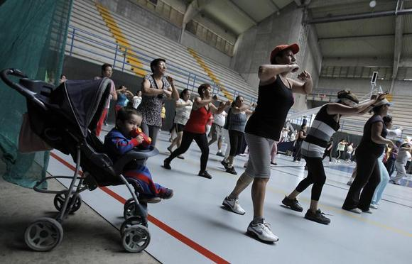 A child waits in his pram while his mother participates in an aerobics class at the gymnasium of a sports center in Cartago, east of San Jose July 10, 2012. REUTERS/Juan Carlos Ulate