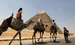 Tourists ride a horse and camels at the Giza Pyramids on the outskirts of Cairo July 24, 2013.REUTERS/Mohamed Abd El Ghany