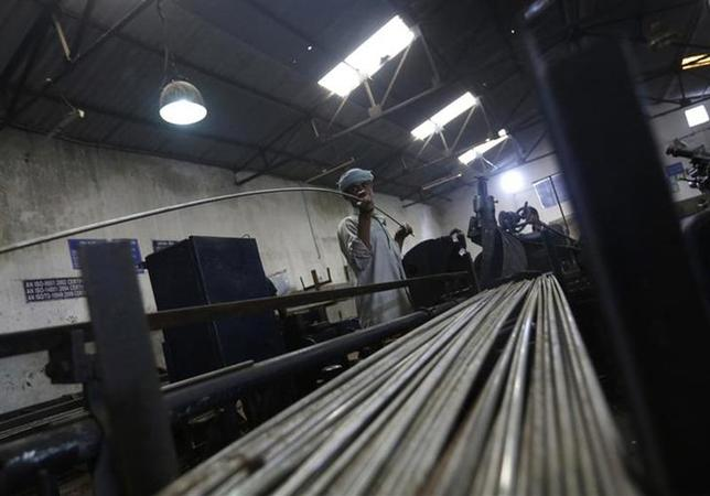 An employee holds a steel rod as he works on the production line inside a steel factory in Bhiwadi September 30, 2013. REUTERS/Adnan Abidi/Files