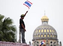 """Антиправительственный демонстрант размахивает флагом Таиланда на демонстрации в Бангкоке 9 декабря 2013 года. Премьер-министр Таиланда Йинглак Чиннават распустила парламент и объявила досрочные выборы, однако лидеры массовых протестов недовольны: они требуют её отставки и передачи власти в стране не выбранному, но назначенному """"народному совету"""". REUTERS/Chaiwat Subprasom"""