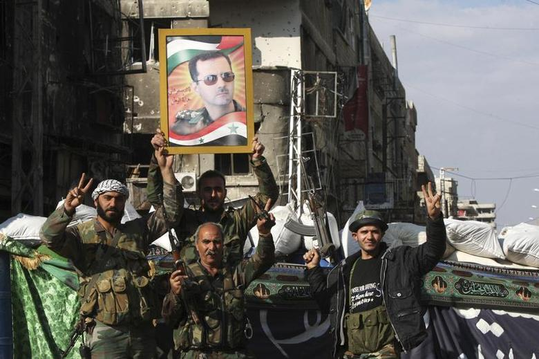 Security personnel loyal to Syria's President Bashar al-Assad flash the 'V' signs in Hujaira town, south of Damascus November 20, 2013 file photo. REUTERS/Alaa Al-Marjani