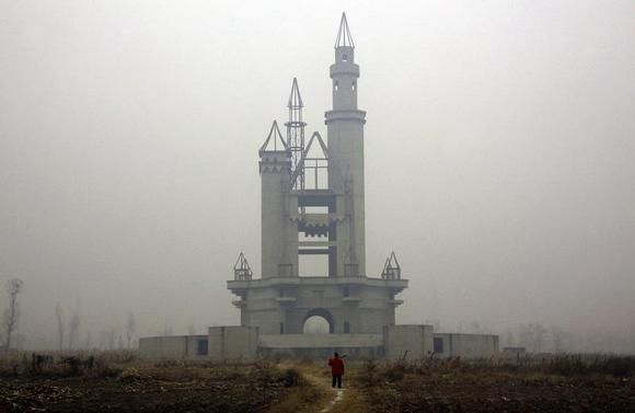 A farmer carries a shovel over his shoulder as he walks to tend his crops in a field that includes an abandoned building, that was to be part of an amusement park called 'Wonderland', on the outskirts of Beijing December 5, 2011. REUTERS/David Gray