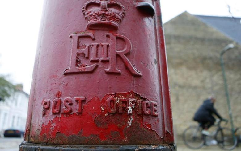 A man rides a bicycle past a post box in London November 27, 2013. REUTERS/Suzanne Plunkett