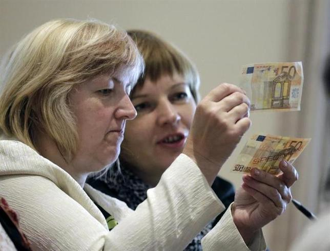People learn to differentiate between original (bottom) and counterfeit euro banknotes during a workshop in Salacgriva September 24, 2013. REUTERS/Ints Kalnins