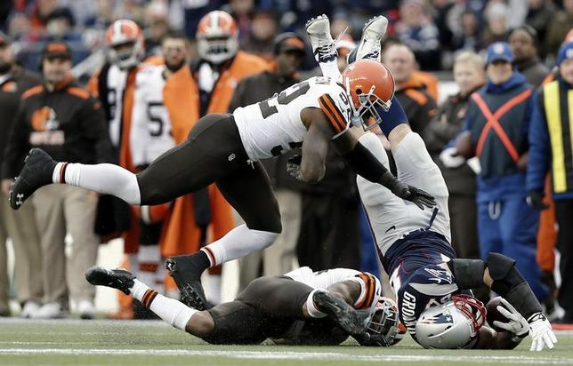 Dec 8, 2013; Foxborough, MA, USA; New England Patriots tight end Rob Gronkowski (87) is tackled by Cleveland Browns strong safety T.J. Ward (43) and inside linebacker D'Qwell Jackson (52) during the third quarter of New England's 27-26 win at Gillette Stadium. Gronkowski left the game and was taken to a hospital after the hit. Mandatory Credit: Winslow Townson-USA TODAY Sports - RTX16A9G