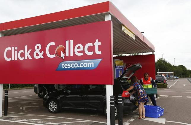 A worker helps a customer load her car with groceries at a Tesco click and collect point in Leicester, central England, August 29, 2013. REUTERS/Darren Staples