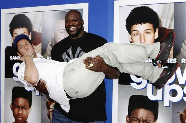 Former NBA star Shaquille O'Neal lifts up cast member Adam Sandler as they arrive for the premiere of the film ''Grown Ups 2'' in New York, July 10, 2013. REUTERS/Lucas Jackson/Files