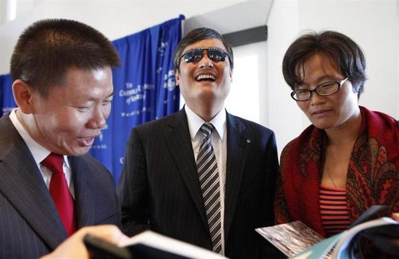 Chinese dissident Chen Guangcheng (C) laughs with wife Yuan Weijing and friend Bob Fu, president of Christian activist group ChinaAid, before a news conference at the National Press Club in Washington October 2, 2013. REUTERS/Yuri Gripas/Files
