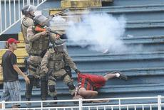 Policemen fire rubber bullets as they help an Atletico Paranaense fan during clashes between Vasco da Gama soccer fans and Atletico Paranaense fans at their Brazilian championship match in Joinville in Santa Catarina state December 8, 2013. REUTERS/Carlos Moraes