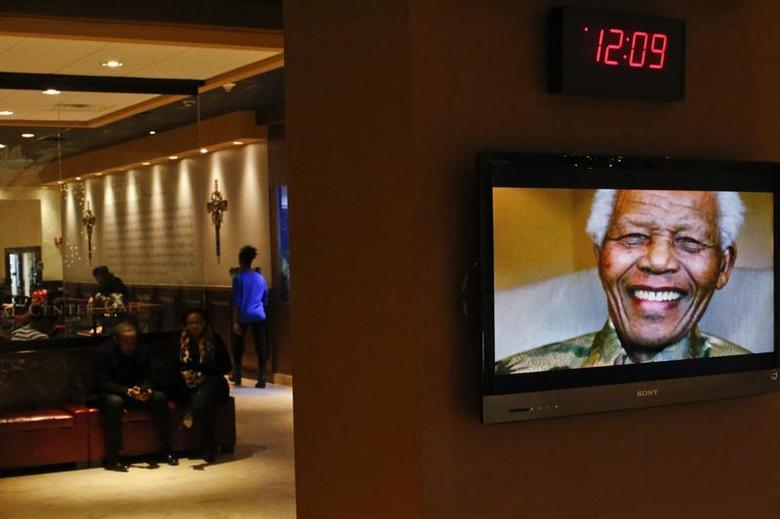 Nelson Mandela is pictured on a display screen as people attend a tribute service for him at the Christian Cultural Center in the Brooklyn area of New York December 8, 2013. REUTERS/Eduardo Munoz