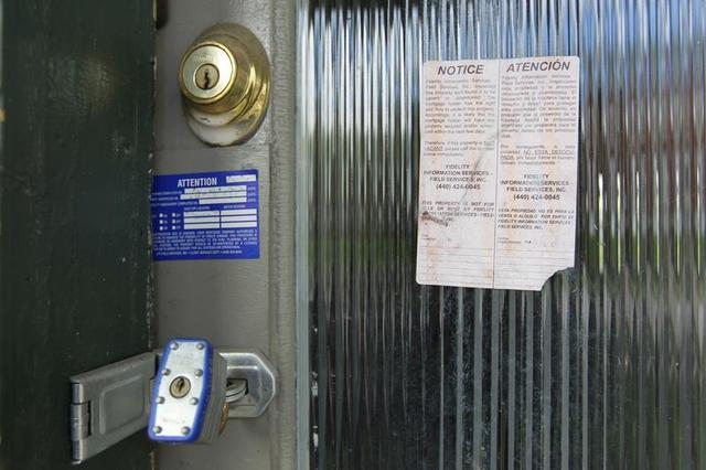 A padlock and foreclosure papers are attached to the front door of a home in the Price Hill neighborhood of Cincinnati, Ohio March 24, 2012. REUTERS/John Sommers II