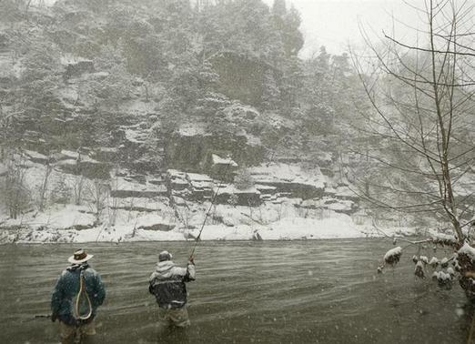 Fly fishermen Mike Gasiecki and guide Dan Soper (L) fish the north fork of the south branch of the Potomac River during a winter blizzard in Hopeville Canyon, West Virginia December 8, 2013. REUTERS/Gary Cameron