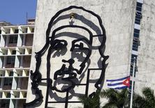 """Rusia y Cuba firmaron calladamente un acuerdo que condona el 90 por ciento de una deuda por 32.000 millones de dólares que La Habana arrastra de la era soviética, un trato que pone fin a una disputa bilateral de 20 años y abre el camino a una mayor inversión y comercio, dijeron diplomáticos rusos y europeos. En la foto de archivo, una bandera cubana ondeando cerca de una imagen de Ernesto """"Che"""" Guevara en La Habana. Dic 6, 2013. REUTERS/Enrique de la Osa"""