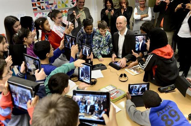 Fifth graders use their iPads to take photos of Sweden's Prime Minister Fredrik Reinfeldt (C) during his visit to Husby School, west of Stockholm, November 21, 2012. Reinfeldt visited the school to learn more about the use of tablets in education. REUTERS/Pontus Lundahl/Scanpix Sweden