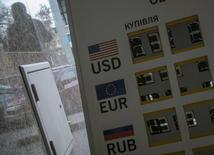 Штендер с курсами валют у обменника в Киеве 16 октября 2013 года. Рубль незначительно подрос к доллару и снизился к евро при открытии биржи, отразив изменения в паре евро/доллар на форексе, и стабилен к бивалютной корзине. REUTERS/Gleb Garanich