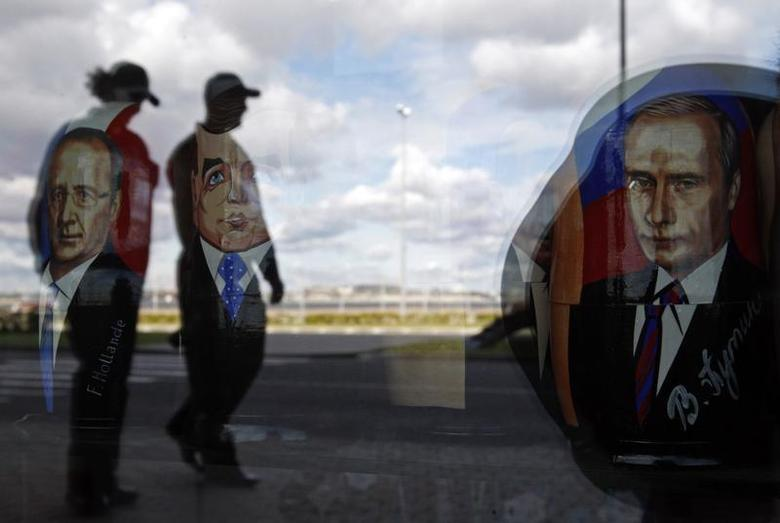 Police are reflected in the window of a shop displaying traditional nesting dolls with images of Russian President Vladimir Putin (R), Prime Minister Dmitry Medvedev (C) and French President Francois Hollande at the sea port in St. Petersburg September 3, 2013. REUTERS/Alexander Demianchuk