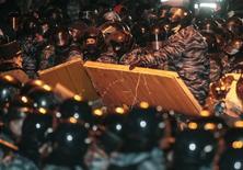 Спецназ милиции разбирает баррикады, возведенные сторонниками евроинтеграции у администрации президента в Киеве 10 декабря 2013 года. Внутренние войска на вторник вытеснили сторонников евроинтеграции из правительственного квартала украинской столицы и взяли под усиленную охрану подъезды к зданию правительства и администрации президента, где Виктор Янукович планирует сегодня начать переговоры о выходе из политического кризиса. REUTERS/Stringer