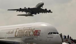 An Airbus A380 aircraft of Deutsche Lufthansa (top) takes of passing over an Airbus A380 aircraft of Emirates at the ILA International Air Show in Schoenefeld south of Berlin, June 8, 2010. REUTERS/Fabrizio Bensch