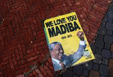 A placard showing a picture of the late South African president Nelson Mandela is seen on the pavement outside the First National Bank (FNB) Stadium, also known as Soccer City, ahead of Mandela's national memorial service on Tuesday in Johannesburg December 10, 2013. REUTERS/Yves Herman