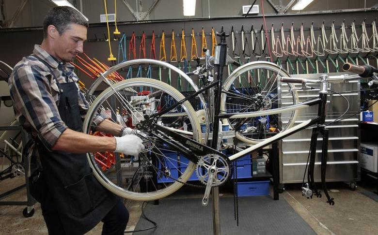Max Stchelcine assembles a Shinola three-speed bicycle at the newly opened Shinola luxury bike and watch store in midtown Detroit, Michigan July 22, 2013. REUTERS/Rebecca Cook