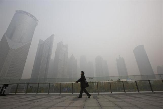 A man wearing a face mask walks on a pedestrian overpass on a hazy day at the Pudong financial area in Shanghai, December 6, 2013. REUTERS/Aly Song