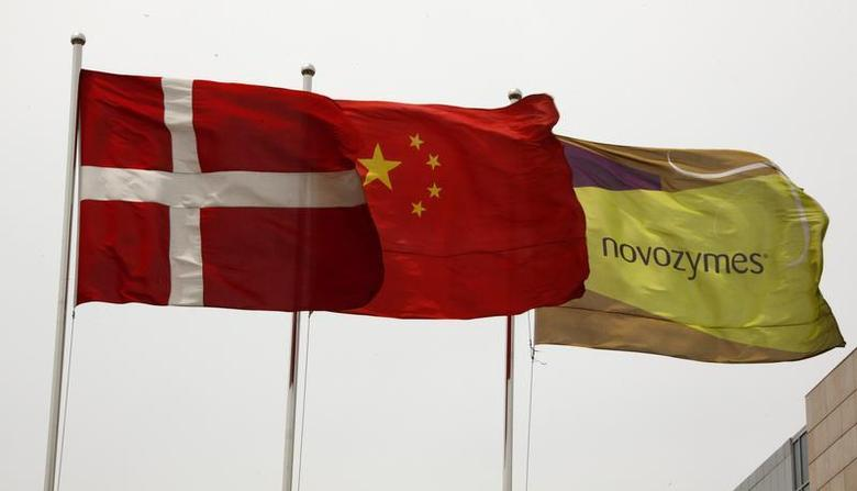 The Danish national flag (L) flies alongside the Chinese national flag (C) and the flag of biopharmaceutical company Novozymes, outside the company's factory located in the Tianjin Economic Development Area (TEDA), 120 kiolemtres southeast of Beijing May 24, 2011. REUTERS/David Gray