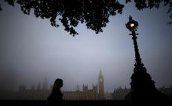 A woman walks along the south bank of the Thames opposite the Houses of Parliament on a foggy morning in London September 24, 2013. REUTERS/Andrew Winning